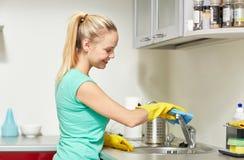 Cucina felice del rubinetto di pulizia della donna a casa Fotografie Stock