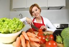 Cucina felice della donna a casa che prepara insalata di verdure con le carote della lattuga e che affetta pomodoro fotografia stock