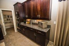 Cucina moderna con il contatore del granito e della dispensa con gli elementi del decoratore fotografia stock