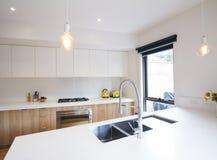 Cucina moderna con illuminazione del pendente ed il lavandino incavato Immagini Stock