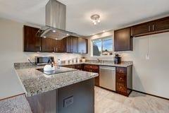 Cucina recentemente rinnovata con i gabinetti e il coun di legno scuri del granito Immagine Stock Libera da Diritti