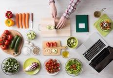 Cucinando a casa con le ricette online fotografie stock