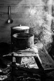 Cucinando in casseruole su una stufa improvvisata sopra un fuoco Fotografie Stock Libere da Diritti