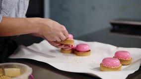 Cucinando, cocendo e concetto della confetteria - il cuoco unico che decora i dolci della glassa dello specchio con dorato spruzz stock footage