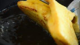 Cucinando con un pane del pane tostato in una pentola con l'ebollizione dell'olio stock footage