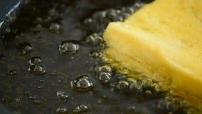 Cucinando con un pane del pane tostato in una pentola con olio che bolle, dettaglio stock footage