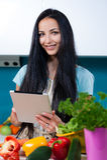 Cucinando e cercare le ricette online Fotografia Stock