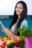 Cucinando e cercare le ricette online Immagini Stock