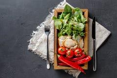 Cucinando gli ingredienti in scatola di legno su fondo scuro, la vista superiore, copia lo spazio Immagini Stock