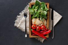 Cucinando gli ingredienti in scatola di legno su fondo scuro, la vista superiore, copia lo spazio Fotografia Stock