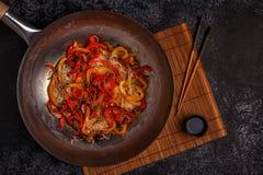 Cucinando il wok asiatico con scalpore frigga le tagliatelle e le verdure fotografia stock