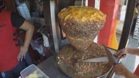 Cucinando la carne sulla friggitrice rotative per lo shawarma, una preparazione araba della carne, carni miste è disposta su uno  video d archivio