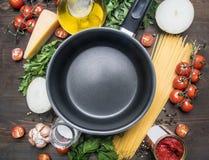 Cucinando la pasta vegetariana con i pomodori ciliegia, prezzemolo, cipolla ed aglio, burro, passata di pomodoro e formaggio, gli fotografia stock libera da diritti