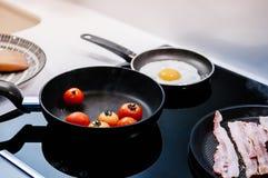 Cucinando la pentola della prima colazione ha grigliato i pomodori, il bacon e l'uovo fritto fotografia stock