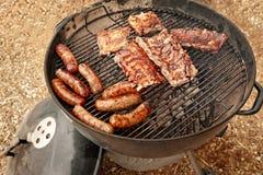 Cucinando le salsiccie e gli scaffali delle costole all'aperto su una griglia rifornita carbone immagini stock