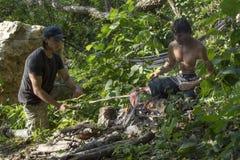 Cucinando sopra il fuoco di accampamento primitivo nella giungla immagini stock libere da diritti