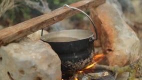 Cucinando su un fuoco di accampamento nella foresta nebbiosa stock footage