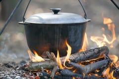 Cucinando sul fuoco di accampamento. Fotografia Stock