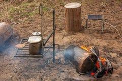 Cucinando sull'attrezzatura del fuoco di accampamento in un campo della tenda immagini stock libere da diritti