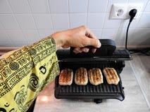 Cucinando sulla griglia elettrica sulla tavola a casa fotografia stock