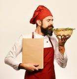 Cucini con il fronte calmo in uniforme di Borgogna tiene il piatto al forno immagini stock