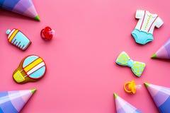 Cucini i biscotti del pan di zenzero con nastro adesivo di cuore per la doccia di bambino sul modello rosa di vista superiore del fotografie stock