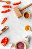 Cucini il posto di lavoro con gli strumenti della cucina ed il modello bianco di vista superiore del fondo dell'aglio Fotografia Stock