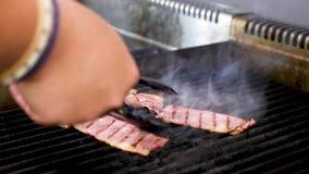 Cucini il turnin delle mani due pezzi di bacon affumicato sulla griglia stock footage