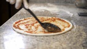 Cucini l'aggiunta della passata di pomodoro con un cucchiaio di cottura alla base della pasta della pizza video d archivio