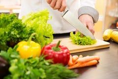 Cucini la lattuga di taglio, preparante l'insalata di verdure in cucina immagini stock