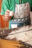 Cucini la mano che fende un uovo in un mucchio di farina fotografie stock