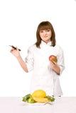 Cucini la ragazza che tiene una lama e un mango Fotografie Stock Libere da Diritti