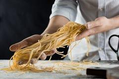 Cucini la tenuta degli spaghetti di recente cucinati nella cucina fotografia stock libera da diritti