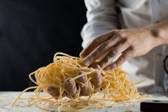 Cucini la tenuta degli spaghetti di recente cucinati nella cucina fotografie stock libere da diritti