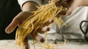 Cucini la tenuta degli spaghetti di recente cucinati nella cucina immagine stock