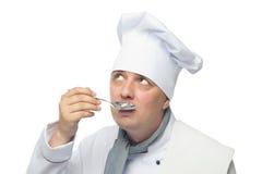 Cucini la tenuta del cucchiaio in sua mano e la prova di avere un sapore fotografie stock libere da diritti