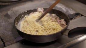 Cucini la tenuta della mescolatura degli spaghetti con la salsa di formaggio ed il bacon tagliato che friggono in pentola calda archivi video