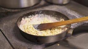 Cucini la tenuta della mescolatura degli spaghetti con la salsa di formaggio ed il bacon tagliato che friggono in pentola calda video d archivio