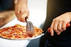 Cucini le mani che tagliano la pizza ai pezzi alla pizzeria Immagini Stock Libere da Diritti