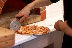 Cucini le mani che tagliano la pizza ai pezzi alla pizzeria Immagini Stock