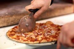 Cucini le mani che tagliano la pizza ai pezzi alla pizzeria Fotografia Stock Libera da Diritti