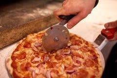 Cucini le mani che tagliano la pizza ai pezzi alla pizzeria Fotografia Stock