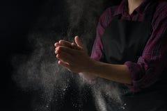Cucini le mani in farina su un fondo nero dell'insegna Fabbricazione pizza, pasta, pane bollente e dei dolci Con un posto vuoto p immagine stock