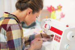 Cucitrice che lavora con la macchina per cucire Isolato su bianco Immagine Stock