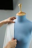 Cucitrice che misura bello tessuto sul manichino blu del sarto nella sua officina Immagini Stock
