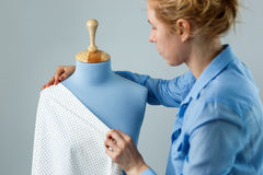 Cucitrice che misura bello tessuto sul manichino blu del sarto nella sua officina Immagine Stock