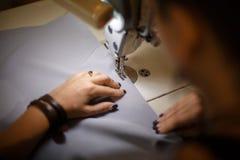 Cucitrice del posto di lavoro Adattamento dell'industria La ragazza cuce sulla macchina per cucire Abbigliamento della fabbrica immagini stock libere da diritti
