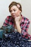 Cucitrice della donna che propone vicino alla macchina per cucire Fotografie Stock
