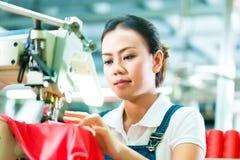 Cucitrice in una fabbrica cinese del tessuto Immagini Stock Libere da Diritti