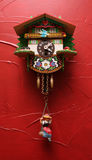 Cuckoo Clock. An antique cuckoo clock hangs on a red wall Stock Image